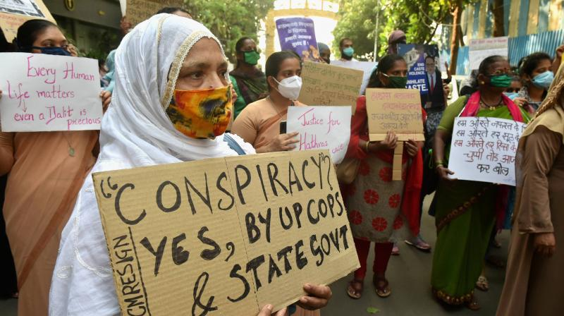 An activist holds a placard during a protest against the Hathras victim, outside Chaitya Bhoomi, in Mumbai. — PTI photo