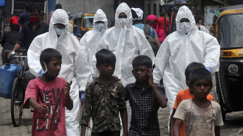 Health workers in PPE suits arrive at a slum in Mumbai to collect samples for COVID tests. — AP photo