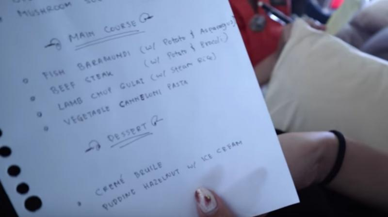 In an embarrassing situation for the flight, the vlog showed that the flight's crew was handing out food menus which were handwritten. (Photo: Youtube I Rius Vernandes)