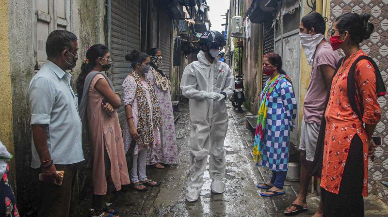Health official takes a body temperature check of a person in Mumbai. (PTI)
