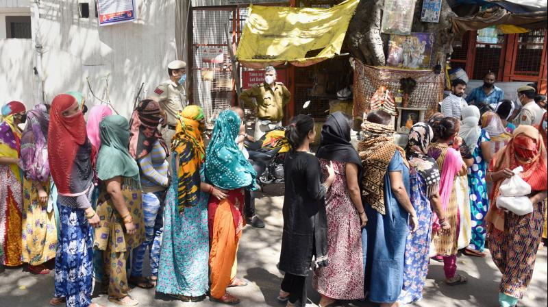 Sex workers queue to collect ration being distributed by the GB Road Market Assosiation during a nationwide lockdown amid the coronavirus outbreak, in New Delhi, Friday. PTI photo