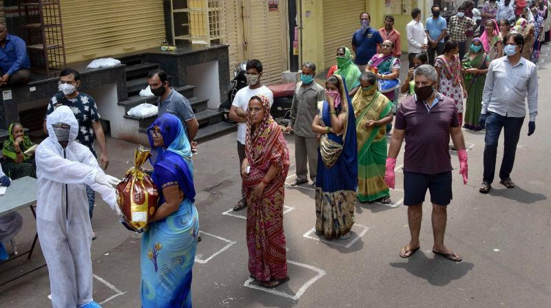 Women queue up maintaining a safe distance to collect their ration. (PTI photo)
