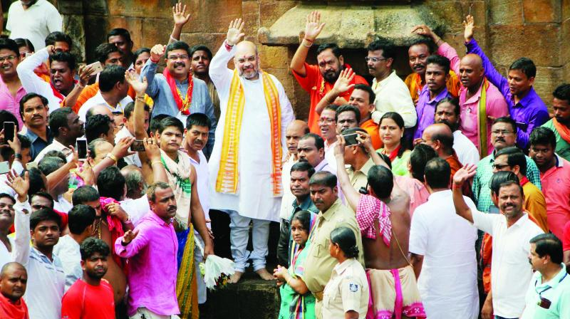 BJP chief Amit Shah waves to supporters during a visit to Lord Lingaraj Temple in Bhubaneswar. (Photo: PTI)
