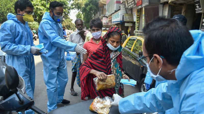 Volunteers distribute packaged food among homeless people during a nationwide lockdown in the wake of coronavirus pandemic, at Kalbadevi area in Mumbai. PTI photo