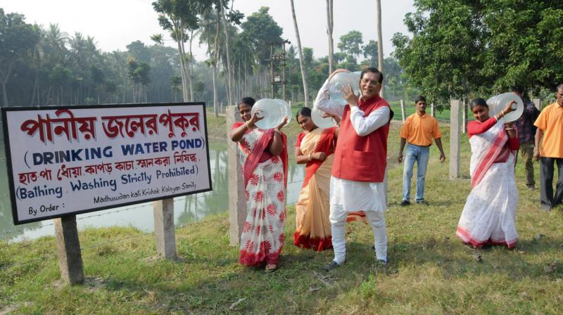 Women along with Dr Bindeshwar Pathak, founder Sulabh International, carrying drinking water cans labelled as 'Sulabh jal' from a water purification plant in  Madhusudan Kati. (Photo: G.N. Jha)