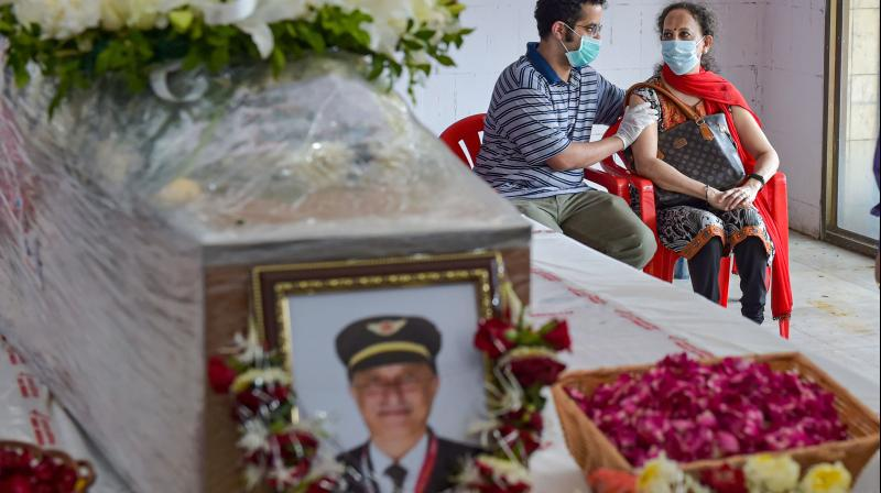 Wife Sushma Sathe and son Dhananjay Sathe of Air India Express pilot Captain Deepak Sathe, grieve as his body was laid out for final respects in Mumbai.(PTI)