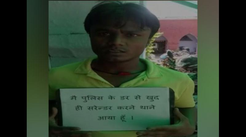 Much to the surprise of police who had launched a search for him, the criminal, Anil walked into the police station here holding a placard that read, 'I have come to the police station on my own, to surrender as I am fearful of police.' (Photo: ANI)