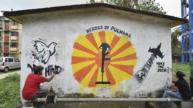 Youth paint a wall to depict IAF's strike on Jaish-e-Mohammed's biggest camp in Pakistan and pay tribute to the slain CRPF jawans of Pulwama terror attack in Kolkata. (Photo: PTI)