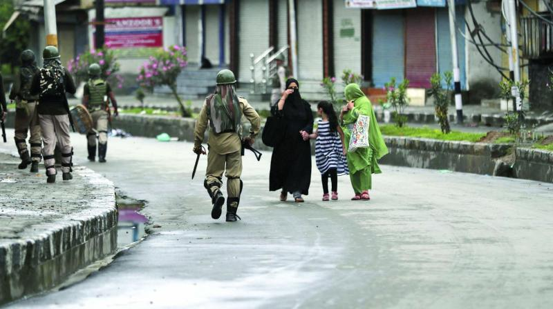 Kashmiris walks past paramilitary troops patrolling a street in Srinagar on Saturday. (Photo: AP)