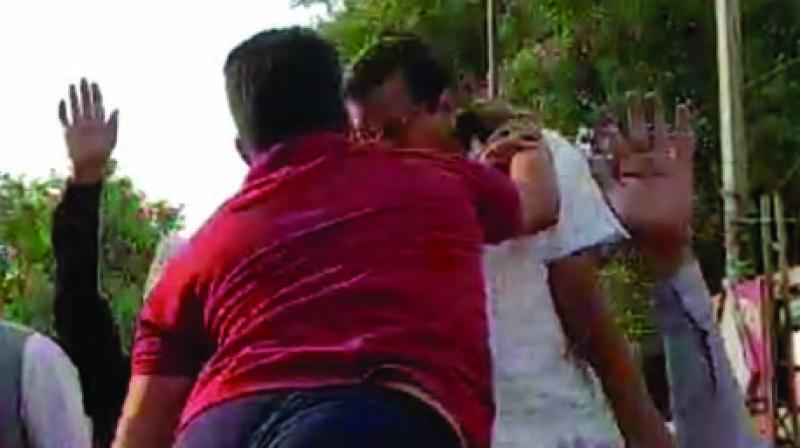 A man climbs atop the open jeep and slaps chief minister Arvind Kejriwal during a roadshow in Moti Nagar on Saturday. Mr Kejriwal was campaigning for New Delhi Lok Sabha seat candidate Brijesh Goyal. (Photo: PTI)