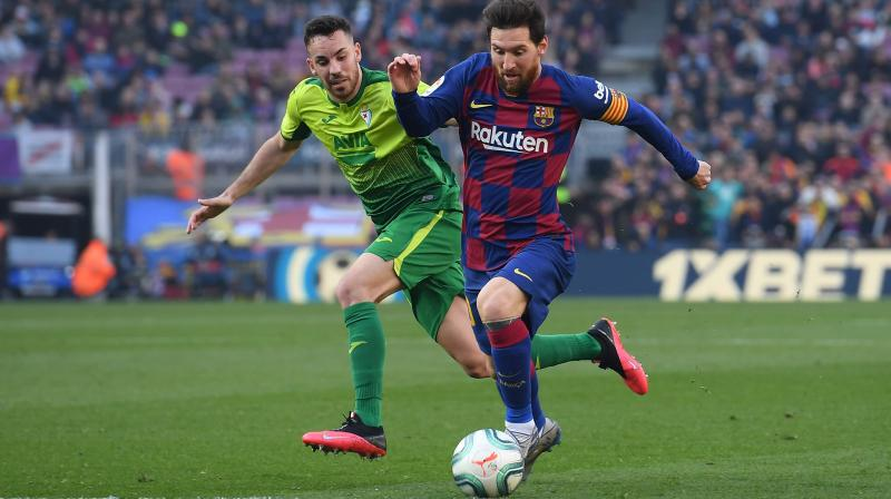 Eibar's Spanish midfielder Edu Exposito (left) challenges Barcelona's Argentine forward Lionel Messi during Barcelona's Spanish league football match against SD Eibar at the Camp Nou stadium in Barcelona on February 22, 2020. (AFP)