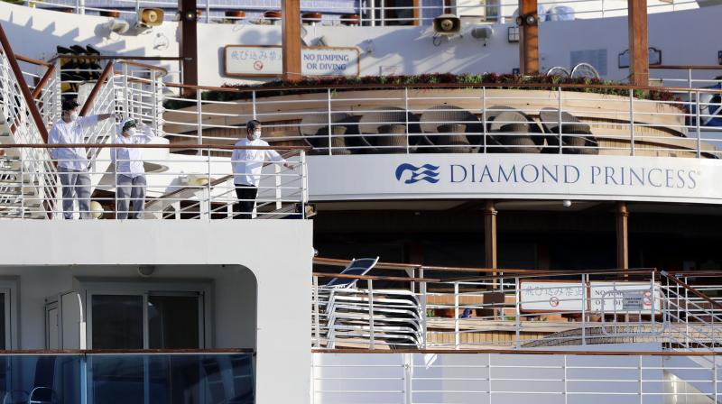 Crews stand on the deck the quarantined ship Diamond Princess anchored at a port in Yokohama, near Tokyo on February 21, 2020. Twelve Indian on the ship have tested positive for the COVID-19 virus. (AP)