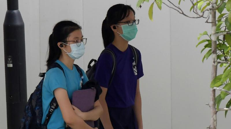 Students wearing face masks, as a preventive measure against the COVID-19 novel coronavirus, walk home from school in Singapore. AFP Photo