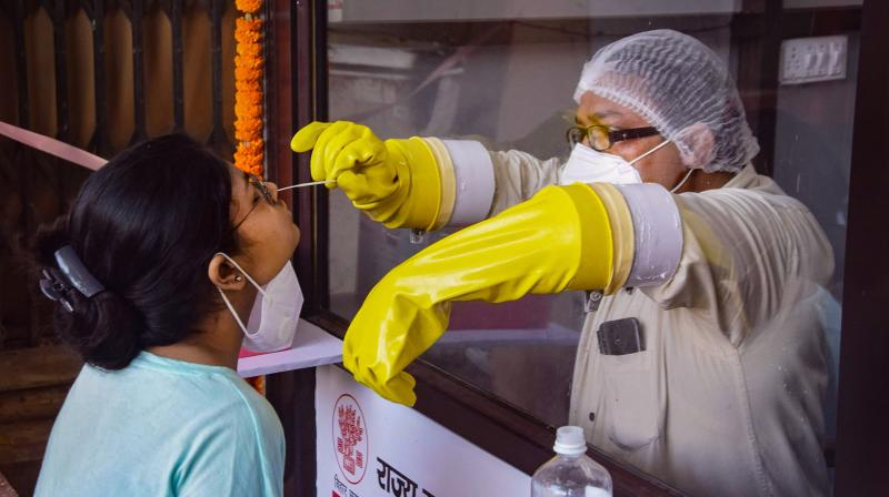 A medic collects samples for COVID-19 testing during total lockdown, in Patna. PTI photo