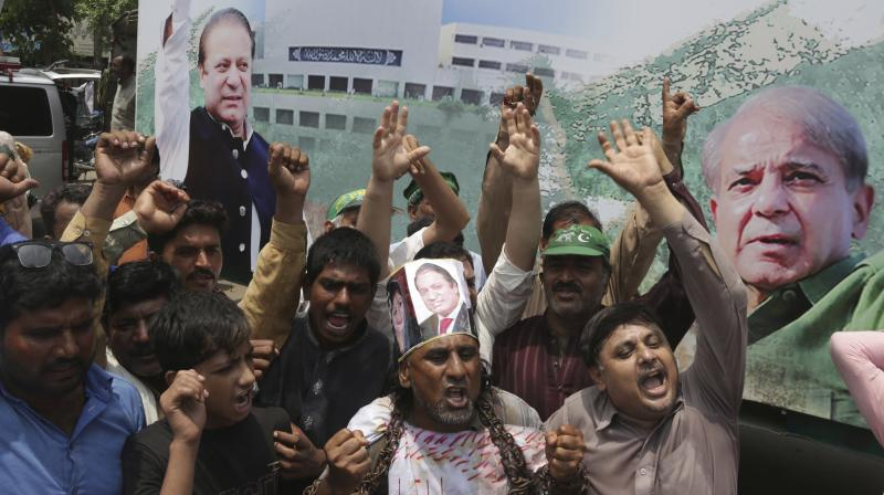 Supporters of Pakistani former prime minister Nawaz Sharif chant slogans for their leader in Lahore, Pakistan on Friday. (Photo: AP)