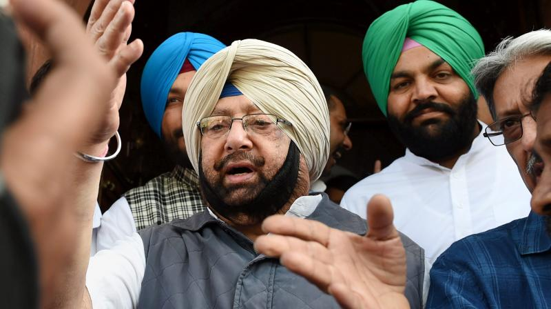 Punjab Chief Minister Amarinder Singh with party MP from Amritsar, Gurjit Singh Aujla (R), after a meeting. (Photo: PTI)