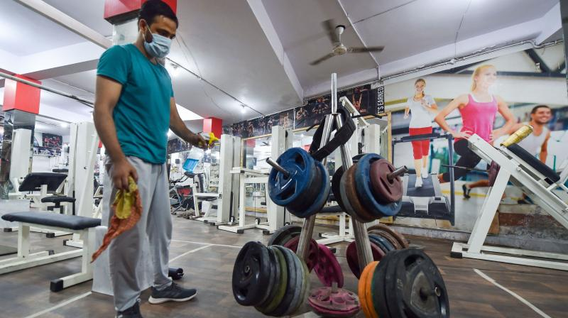 A gym owner sprays disinfectants on equipment after authorities allowed opening of gym and yoga centres with certain restrictions, amid the ongoing coronavirus pandemic, in New Delhi. — PTI photo