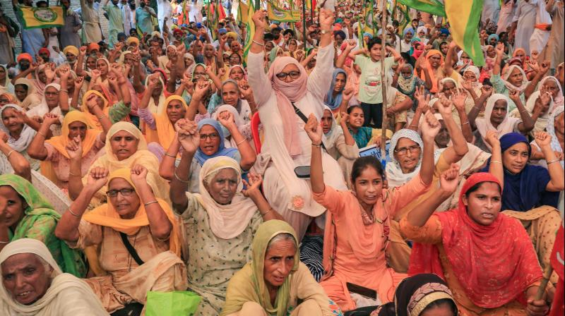 Women raise slogan during a protest against three ordinances passed by the Centre, amid the ongoing coronavirus pandemic, at Badal village in Sri Muktsar Sahib. — PTI