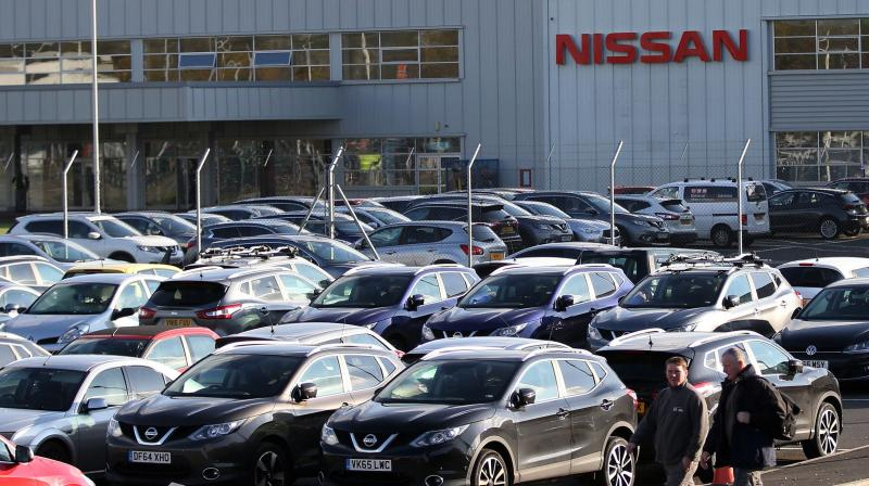 Workers leave the Nissan car plant after finishing their shift. (Photo- AFP)