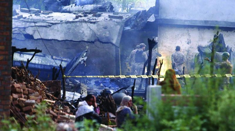 Pakistan Army officials examine the site of a plane crash in Rawalpindi on Tuesday. (Photo: AP)