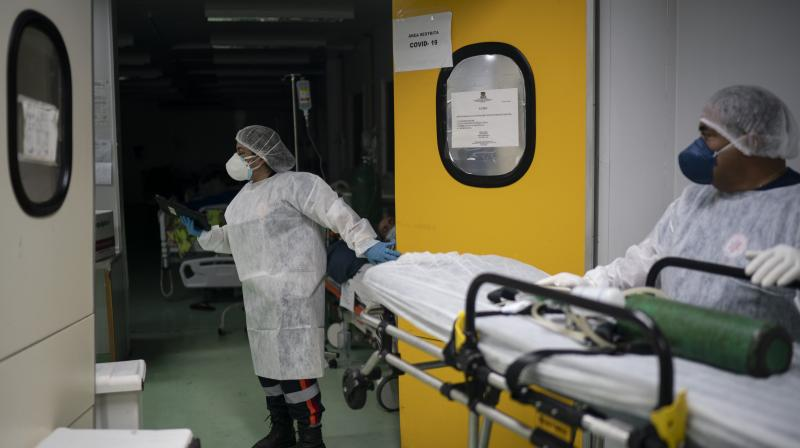Mobile Emergency Care Service (SAMU) workers Gabrielle Carlos, center, and Joao Vericimo enter the COVID-19 area of a hospital as they prepare to move a patient in Duque de Caxias, Rio de Janeiro state, Brazil, Tuesday, April 6, 2021. (AP)