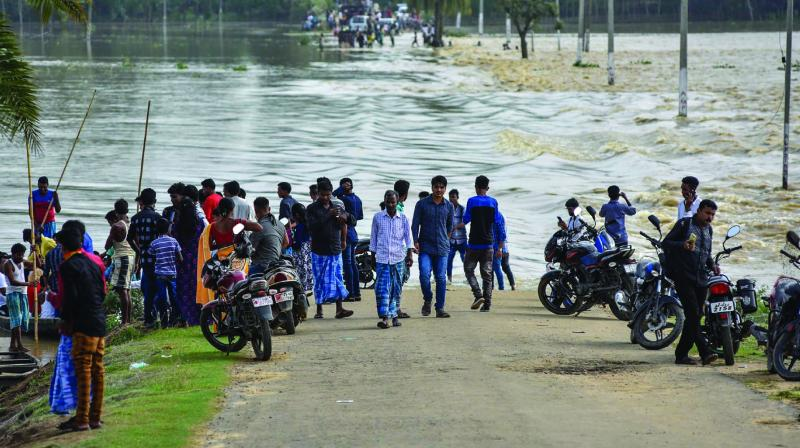 Villagers stand near a partially-submerged road in flood-affected Hojai district of Assam on Saturday. (Photo:PTI)