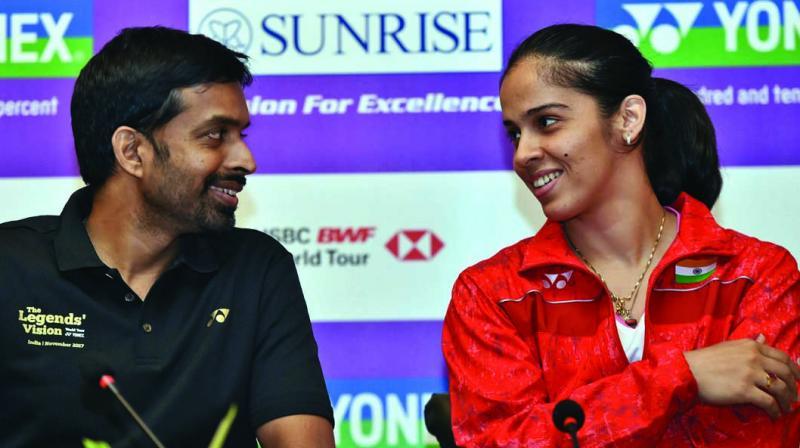 India badminton coach Pullela Gopichand (left) with Saina Nehwal in New Delhi on Tuesday. (Photo:PTI)