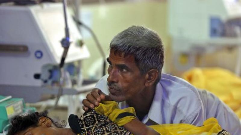 A relative attends to a child receiving treatment at the state-run Baba Raghav Das Medical College Hospital in Gorakhpur, Uttar Pradesh. Acute encephalitis syndrome is a catch-all term to describe patients suffering fever, vomiting, headaches and brain function issues such as confusion, trouble speaking and coma along with seizures. (Photo: AP)
