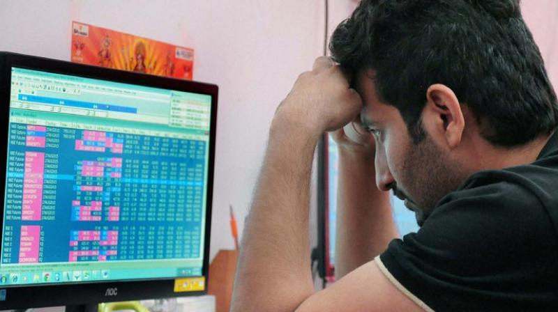 A Broker checks changing share prices at BSE. (Photo: PTI)