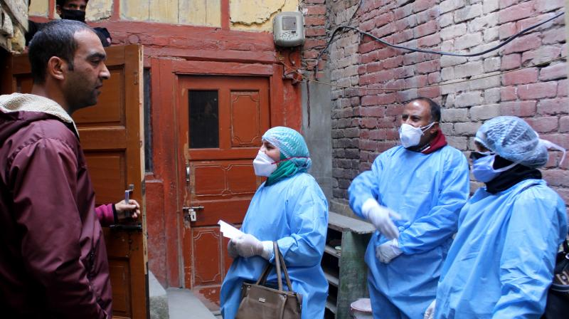 File photo of health staff carrying out a door-to-door campaign in Khanyar locality of Srinagar. The first patient to test positive for the coronavirus was from this locality. On Thursday a person who had flown on the same flight as the first positive also tested positive for coronavirus. (DC Photo by H U Naqash)