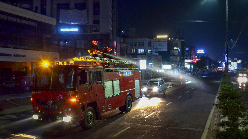 Assam State Fire and Emergency Service workers spray disinfectant at GS Road in Guwahati on March 25, 2020. (PTI)