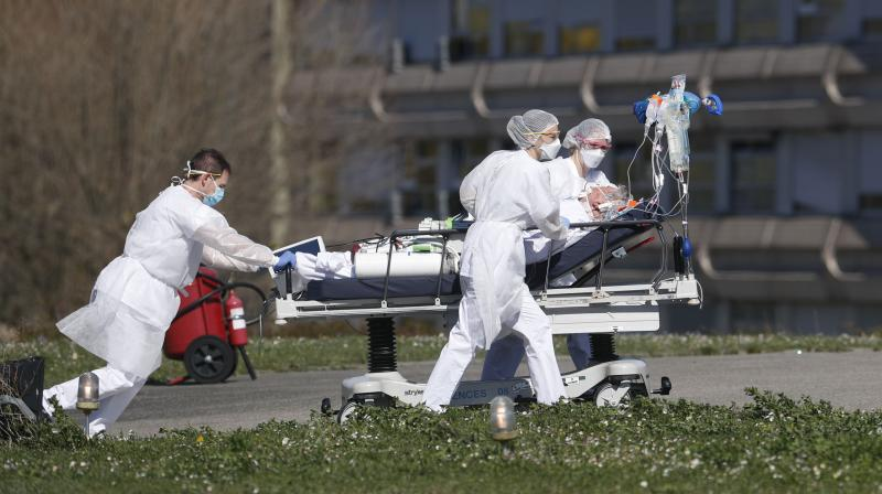 A victim of the COVID-19 coronavirus is evacuated by stretcher from the Mulhouse Civil Hospital in eastern France on March 23, 2020. The Grand Est region has become the epicentre of the outbreak in France. (AP)