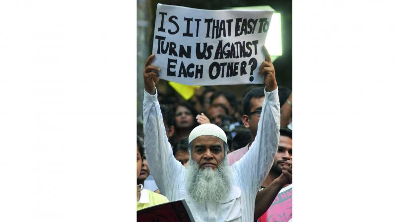 A person holds a placard during a protest at Jantar Mantar on Wednesday. (Photo: Bunny Smith)