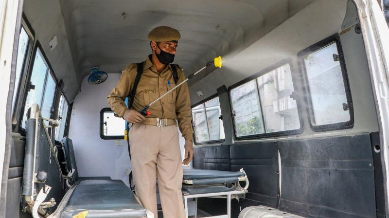 A police personnel spray disinfectants inside a vehicle as a precautionary measure during the nationwide lockdown imposed in the wake of coronavirus pandemic, in Jammu on Monday. PTI photo