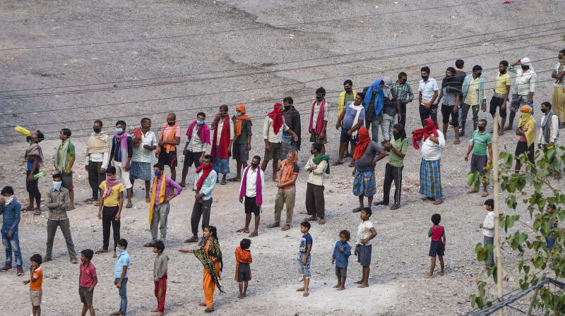 People stand in queue to receive food distributed by volunteers in New Delhi. PTI photo