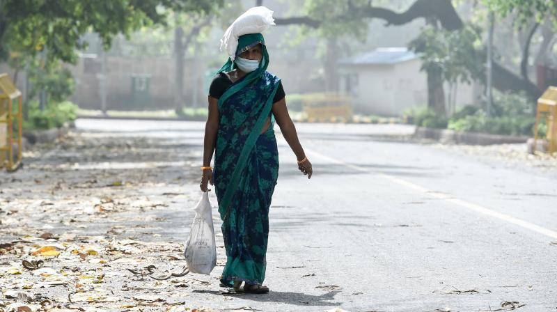 A woman carries essentials to her home during ongoing COVID-19 lockdown in New Delhi. PTI photo