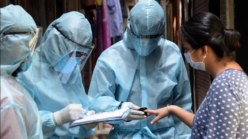 Health workers record the details of a woman during screening for coronavirus infection in Ramabhai Ambedkar Nagar in Ghatkopar East in Mumbai. (DC Photo: Rajesh Jadhav)