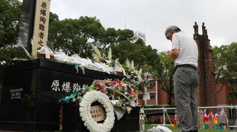 An atomic bomb survivor offers a prayer for the atomic bomb victims in front of the cenotaph at Nagasaki Hypocenter Park. (AFP Photo)