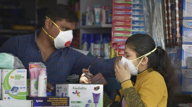 A salesman at a chemist shop helps a buyer wear her protective mask, in wake of the deadly novel coronavirus, outside Safdarjung Hospital, in New Delhi. PTI photo