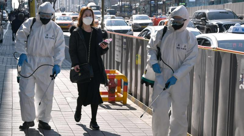 A woman walks past South Korean soldiers wearing protective gear as they spray disinfectant on the street to help prevent the spread of the COVID-19 coronavirus, at Gangnam district in Seoul. AFP photo