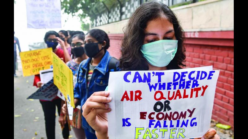 People wear masks during a protest in New Delhi on Sunday, demanding the implementation of measures to reduce air pollution. (Photo: PTI)