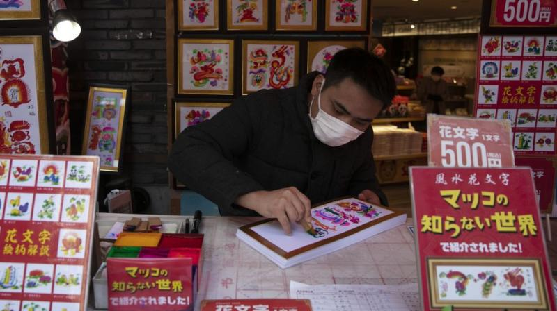 A vendor wears a mask while writing calligraphy for customers in Yokohama's Chinatown, near Tokyo. AP photo
