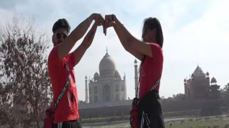 A couple display the love symbol at the famed Taj Mahal in Agra. ANI photo