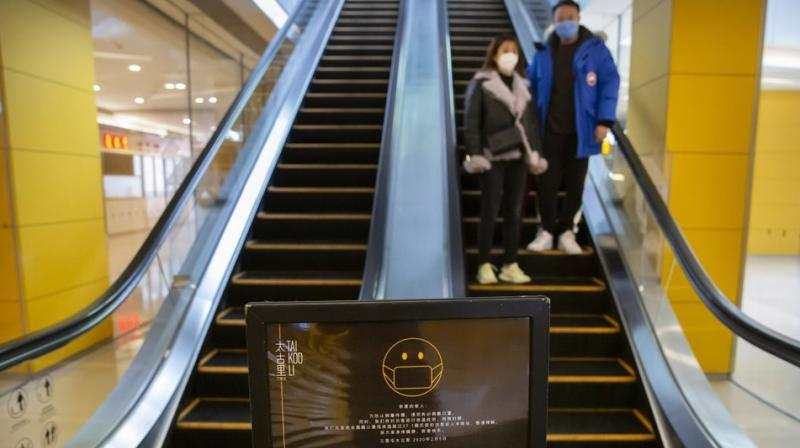 A sign reminds customers to wear face masks as a couple rides an escalator at a shopping center in Beijing, Friday, Feb. 14, 2020. China on Friday reported another sharp rise in the number of people infected with a new virus. AP photo