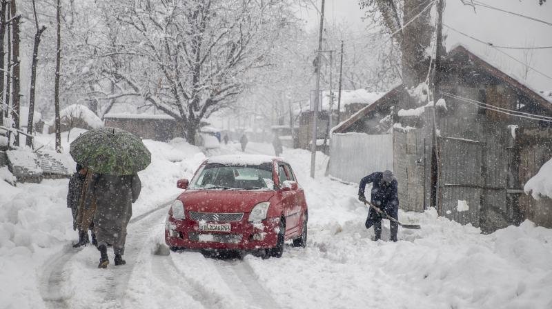 A Kashmiri villager clears snow near the entrance of his house to make way for his car as it snows in Pulwama, south of Srinagar, Indian controlled Kashmir, Tuesday, January. 5, 2021. (AP/ Dar Yasin)