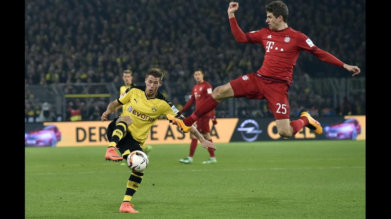 Bayern's Thomas Mueller (R) and Dortmund's Julian Weigl challenge for the ball during the German Bundesliga match. AP Photo