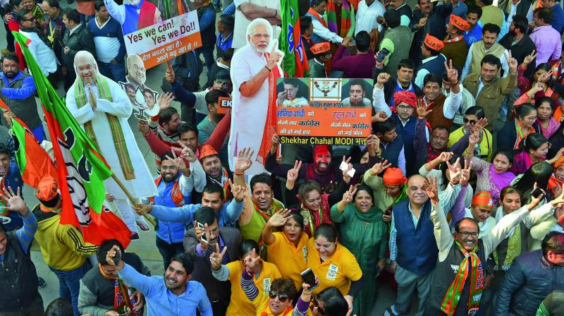 BJP workers celebrate with cut-outs of Prime Minister Narendra Modi and party president Amit Shah at the party headquarters in New Delhi on Monday after the party's victory in the Assembly elections in Gujarat on Himachal Pradesh. (Photo: PTI)