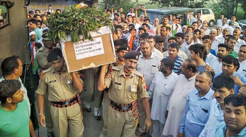 BSF soldiers carry the body of head constable Narendra Singh after it arrived in his native village in Sonipat, Haryana, on September 20. (Photo: PTI)