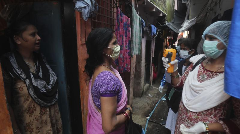A health worker screens people for symptoms of COVID-19 in Dharavi, one of Asia's biggest slums, in Mumbai. (AP)