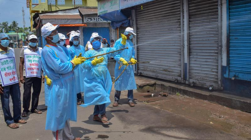 Members of an organization sanitize a market place during the bi-weekly lockdown in the wake of coronavirus pandemic, in Nadia. (PTI)